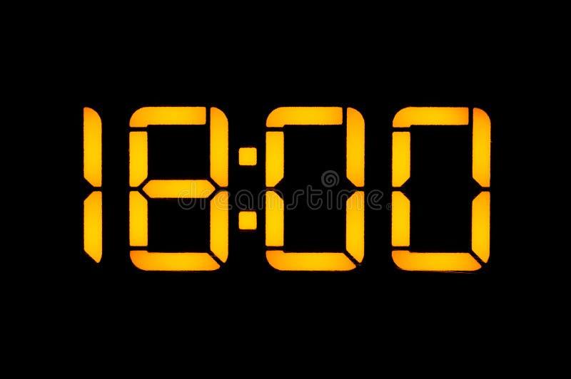 Το ηλεκτρονικό ψηφιακό ρολόι με τους πορτοκαλιούς αριθμούς σε ένα μαύρο υπόβαθρο παρουσιάζει το χρόνο Δεκαοχτώ μηδέν μηδέν το βρά στοκ εικόνες