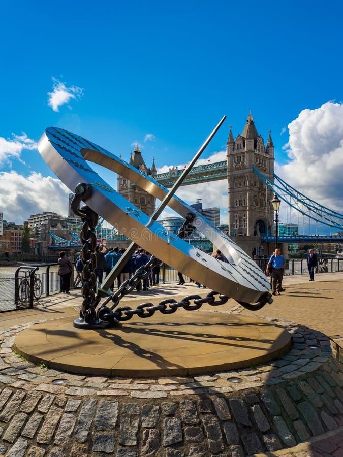 Το ηλιακό ρολόι στις αποβάθρες του ST Katharine και γέφυρα πύργων πέρα από τον ποταμό Τάμεσης στο Λονδίνο, UK μια ηλιόλουστη ημέρ στοκ φωτογραφίες με δικαίωμα ελεύθερης χρήσης