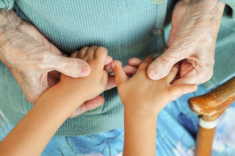Το ηλικιωμένα χέρια παιδιών ` s εκμετάλλευσης γυναικών, ένας ξύλινος κάλαμος στην οδό μεγάλος-γιαγιά και μεγάλος-εγγονός στοκ εικόνα