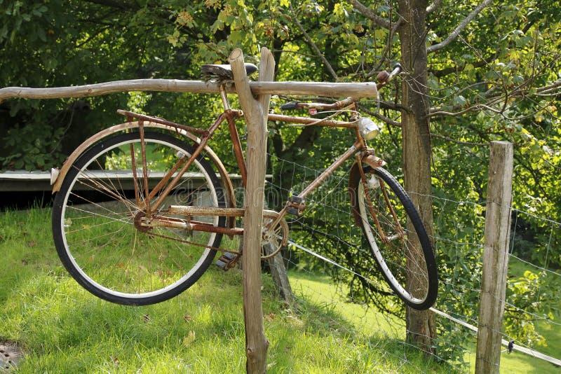 Το ηλικιωμένο άτομο, σκουριασμένο ποδήλατο, κρεμά σε μια ξύλινη ακτίνα στοκ φωτογραφία