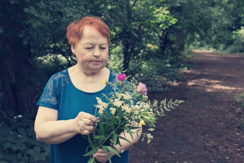 Το ηλικιωμένο πάρκο γυναικών ανθίζει την ανθοδέσμη χεριών στοκ εικόνα με δικαίωμα ελεύθερης χρήσης