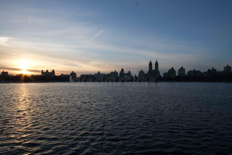 Το ηλιοβασίλεμα απεικονίζει στα κτήρια λιμνών και σκιαγραφιών με το μπλε ουρανό στοκ φωτογραφία με δικαίωμα ελεύθερης χρήσης