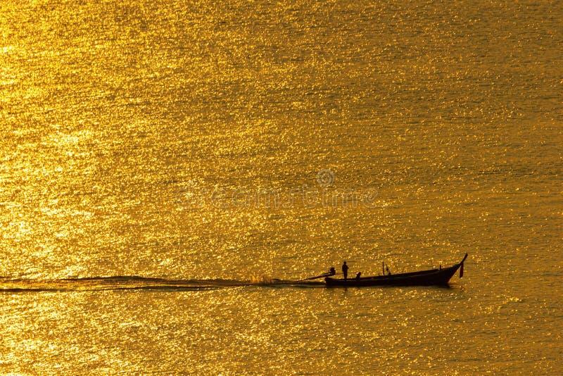 Το ηλιοβασίλεμα, η επιφάνεια θάλασσας απεικονίζει το φως του ήλιου στο χρυσό Το σκάφος έτρεξε μέσω της επιφάνειας θάλασσας σπινθη στοκ εικόνες