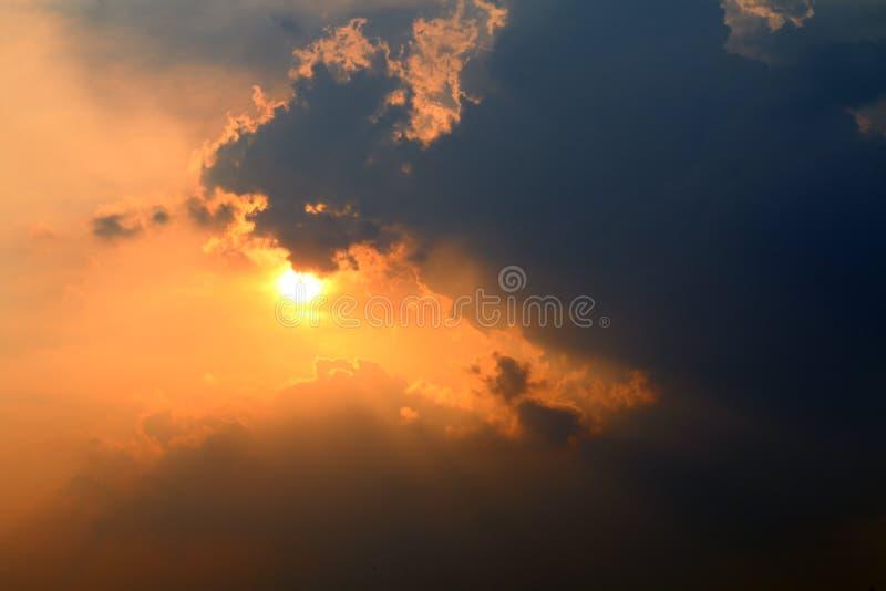 Το ηλιοβασίλεμα, πορτοκαλιά σύνολα ήλιων ουρανού πέρα από το σκοτεινό, χρυσό ήλιο ουρανού σύννεφων φωτίζει να εξισώσει σύννεφων στοκ εικόνες με δικαίωμα ελεύθερης χρήσης