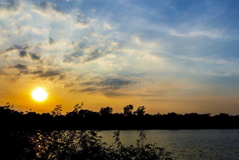 Το ηλιοβασίλεμα στο χρόνο λυκόφατος με τα σύννεφα και τον ήλιο λάμπει μέσω του ρ στοκ φωτογραφίες