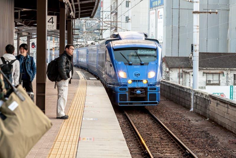 Το ηχιτικό 883 περιορισμένο σαφές τραίνο JR Kyushu είναι πλησιάζοντας σιδηροδρομικός σταθμός Beppu στοκ εικόνες