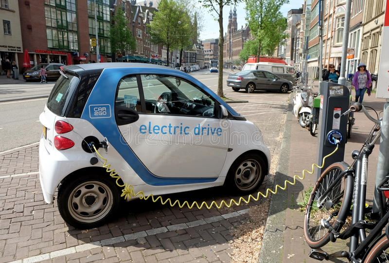 Το ηλεκτρικό αυτοκίνητο χρεώνει σε ένα σημείο στην οδό στοκ εικόνες