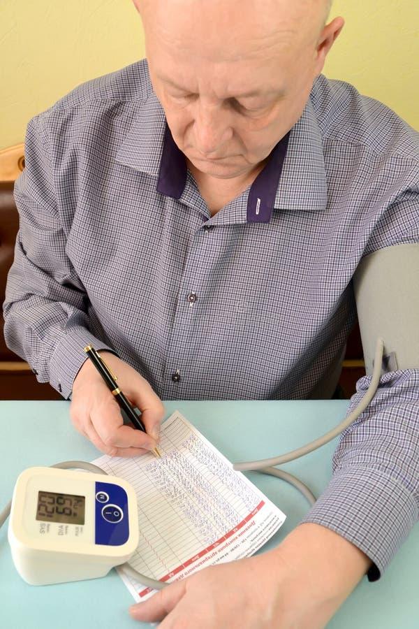 Το ηλικιωμένο άτομο γράφει κάτω τους δείκτες στο ημερολόγιο του ελέγχου της αρτηριακής πίεσης στοκ φωτογραφίες