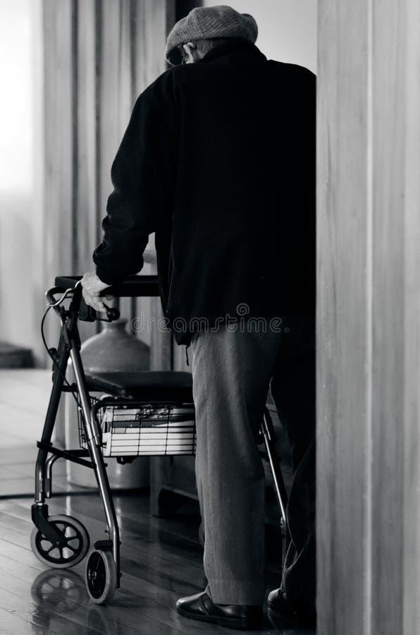 Το ηλικιωμένο άτομο χρησιμοποιεί έναν περιπατητή (πλαίσιο περπατήματος) στοκ εικόνα με δικαίωμα ελεύθερης χρήσης