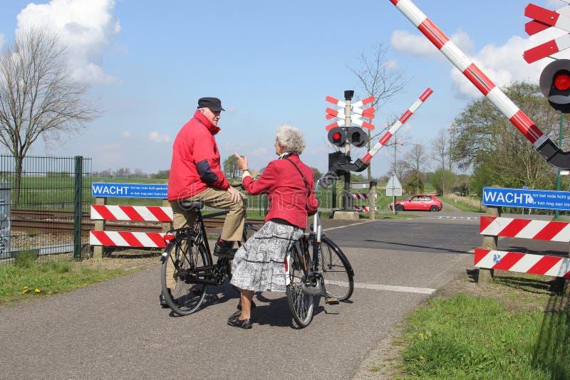Το ηλικιωμένο ζεύγος στα ποδήλατα περιμένει στο πέρασμα σιδηροδρόμων στοκ εικόνες