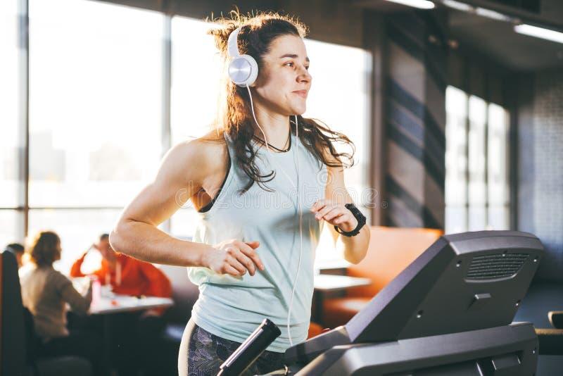 Το θέμα είναι αθλητισμός και μουσική Τρεξίματα όμορφα διογκωμένα γυναικών στη γυμναστική treadmill Σε την επικεφαλής είναι μεγάλα στοκ φωτογραφίες με δικαίωμα ελεύθερης χρήσης