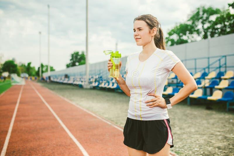 Το θέμα είναι αθλητισμός και υγεία Η όμορφη νέα καυκάσια γυναίκα με το μεγάλο δρομέα αθλητών στηθών στέκεται στο τρέξιμο στοκ φωτογραφίες