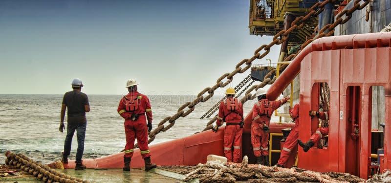 Το θαλάσσιο πλήρωμα παρατηρεί την αλυσίδα για τις επιπλέουσες αποθήκες παραγωγής fpso και το ξεφόρτωμα στοκ φωτογραφίες