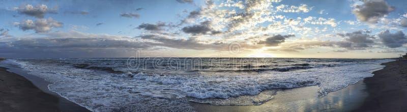 Το θεαματικό πανοραμικό ηλιοβασίλεμα στη ρωμαϊκή ακτή σε Ostia Lido με τα κύματα που σπάζουν στην ακτή και τον μπλε και χρυσό ουρ στοκ φωτογραφία με δικαίωμα ελεύθερης χρήσης
