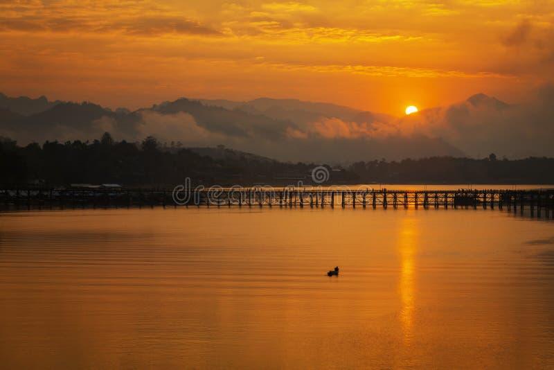 Το θερινή ηλιοβασίλεμα ή η ανατολή πέρα από τη γέφυρα Mon είναι η μακριά ξύλινη γέφυρα Γέφυρα Attanusorn Είναι η διαδρομή του στα στοκ εικόνα