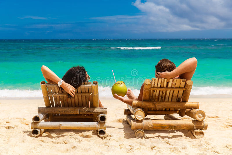 Το θερινό ζεύγος παραλιών στις διακοπές διακοπών νησιών χαλαρώνει στον ήλιο στοκ εικόνες