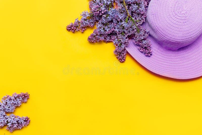 Το θερινό ρόδινο καπέλο γυναικών s και μια ανθοδέσμη των ιωδών λουλουδιών ανθίζουν σε ένα κίτρινο υπόβαθρο επιλεγμένη εστίαση στοκ εικόνα