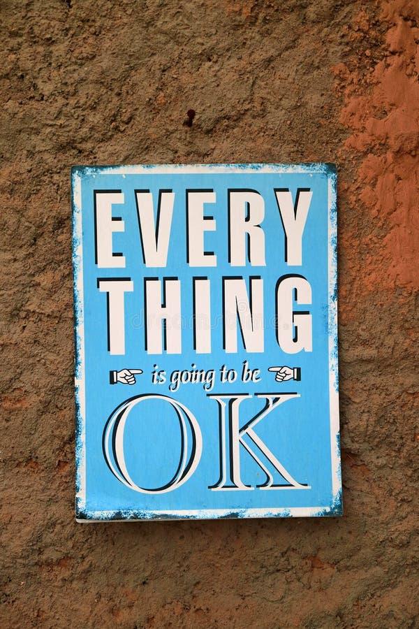 Το θετικό απόσπασμα ΟΛΩΝ πρόκειται να είναι ΕΝΤΑΞΕΙ στο μπλε πιάτο που κρεμά στον τραχύ καφετή τοίχο στοκ φωτογραφία με δικαίωμα ελεύθερης χρήσης
