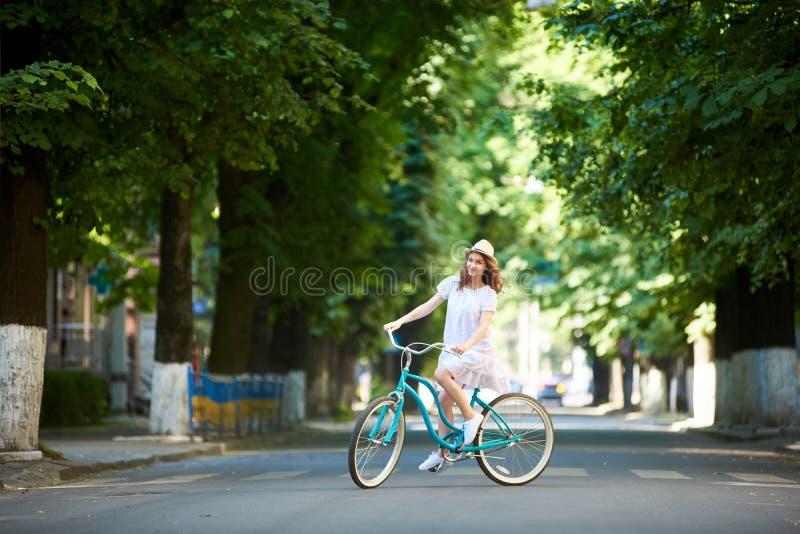 Το θετικό όμορφο κορίτσι στο άσπρο καπέλο φορεμάτων και αχύρου είναι ευτυχές οδηγώντας μπλε ποδήλατο κάτω από την ευρεία όμορφη α στοκ εικόνα με δικαίωμα ελεύθερης χρήσης