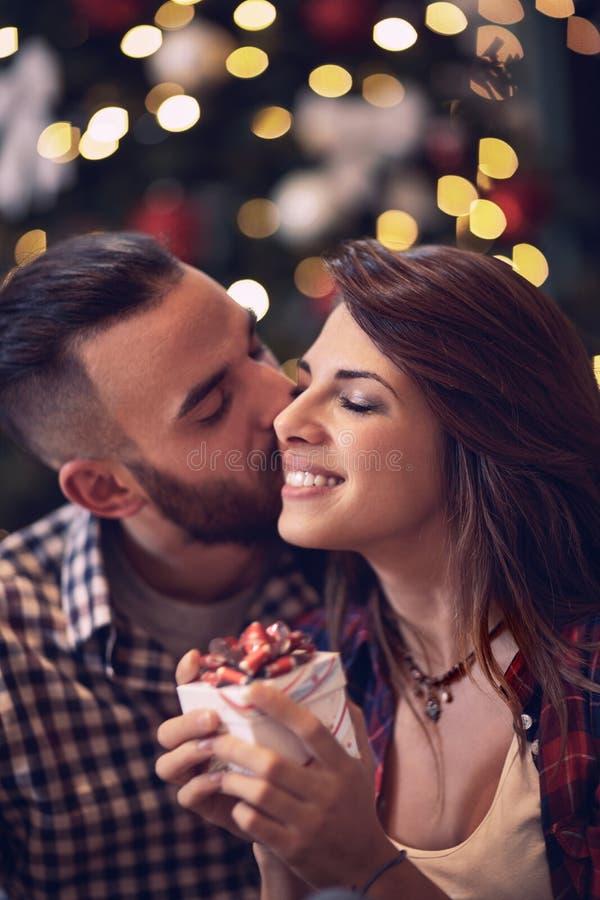 Το θηλυκό απολαμβάνει στο φιλί και το δώρο για τα Χριστούγεννα στοκ φωτογραφίες