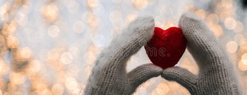 Το θηλυκό παραδίδει τα πλεκτά άσπρα γάντια με την καρδιά του χιονιού στη χειμερινή ημέρα στοκ εικόνες