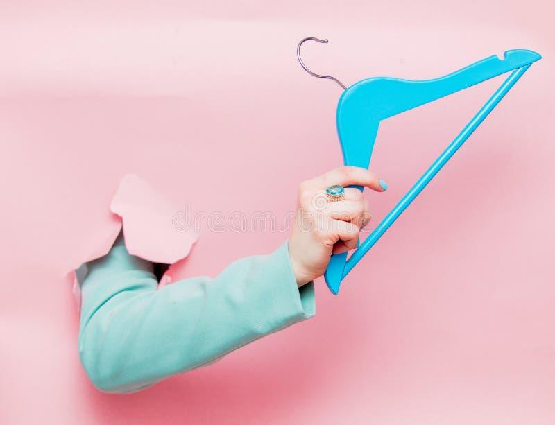 Το θηλυκό παραδίδει την κλασική μπλε ζακέτα με την κρεμάστρα στοκ φωτογραφίες με δικαίωμα ελεύθερης χρήσης