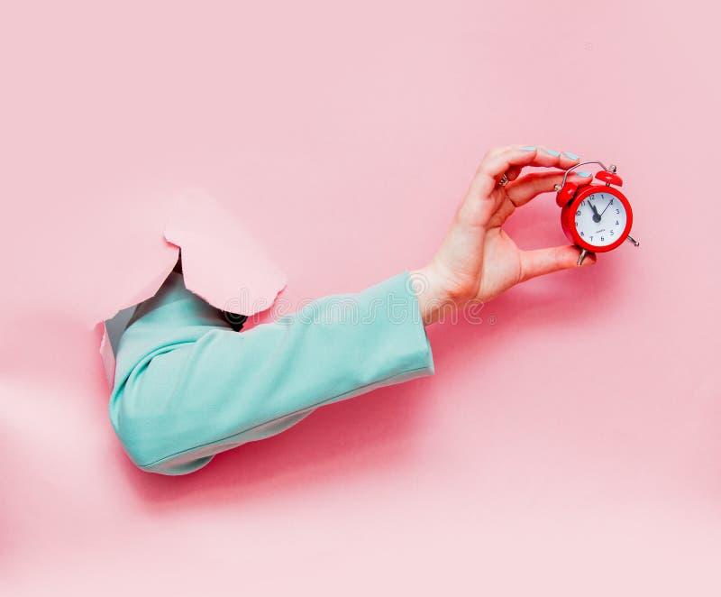 Το θηλυκό παραδίδει την κλασική μπλε ζακέτα με το κόκκινο ξυπνητήρι στοκ εικόνες