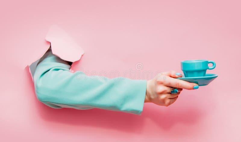 Το θηλυκό παραδίδει την κλασική μπλε ζακέτα με το φλιτζάνι του καφέ ή το τσάι στοκ φωτογραφία