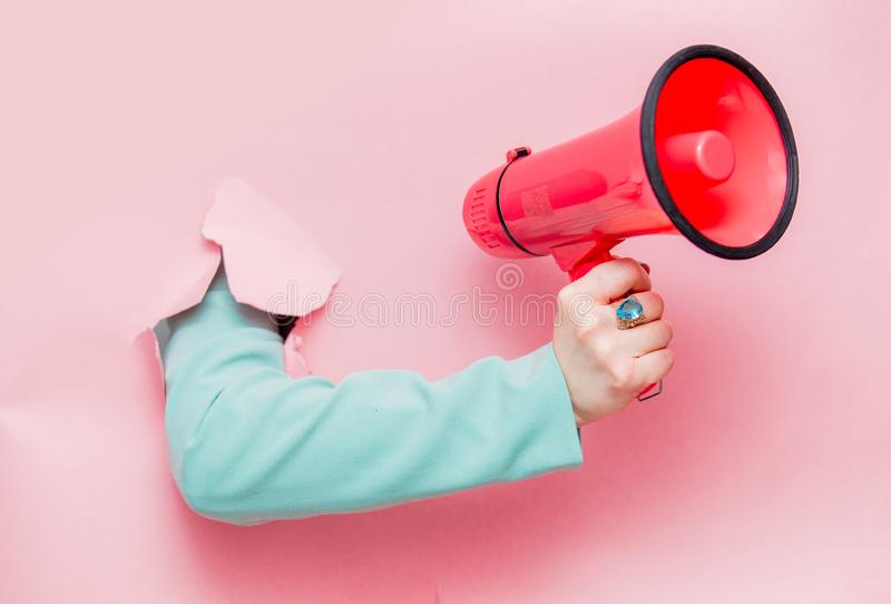 Το θηλυκό παραδίδει την κλασική μπλε ζακέτα με megaphone στοκ φωτογραφία