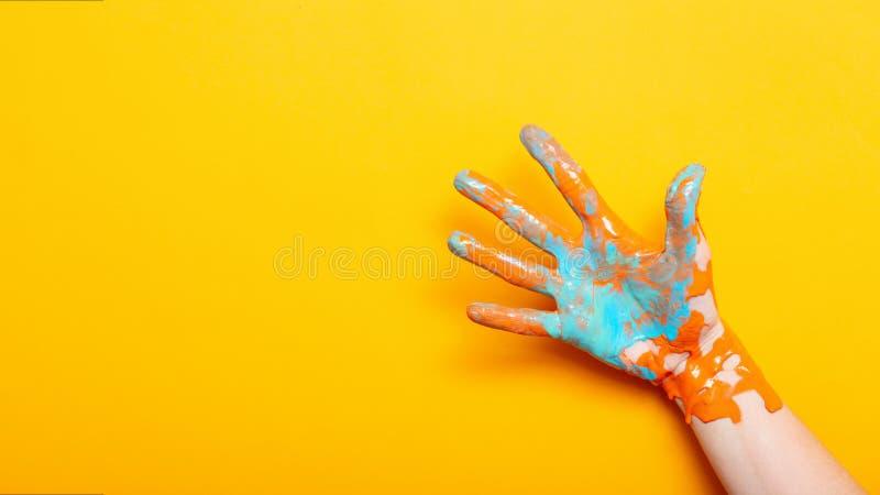 Το θηλυκό παραδίδει το χρώμα σε ένα κίτρινο υπόβαθρο, δημιουργική ιδέα της διαφήμισης, χειρονομία πέντε φοινικών στοκ εικόνες