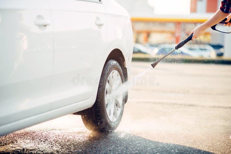 Το θηλυκό πρόσωπο καθαρίζει τις ρόδες αυτοκινήτων με το πυροβόλο όπλο νερού στοκ εικόνες