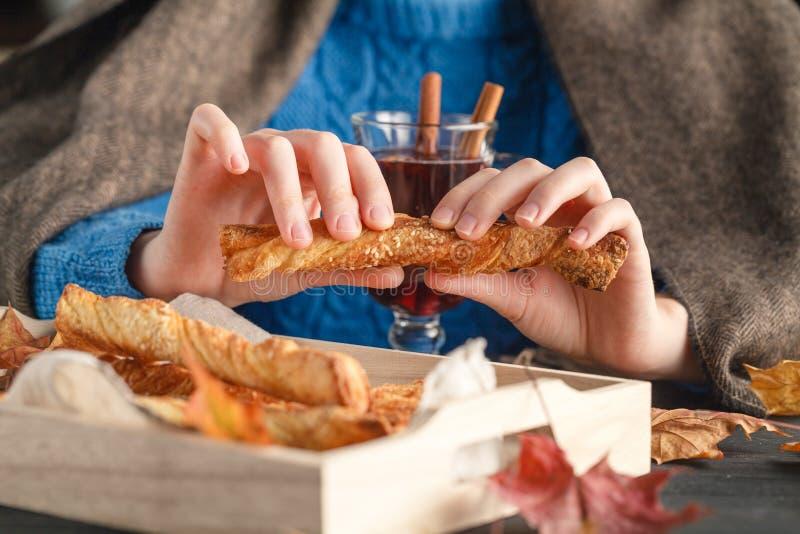 Το θηλυκό στο άνετο κάλυμμα τρώει τα μπισκότα στον πίνακα στοκ εικόνα με δικαίωμα ελεύθερης χρήσης