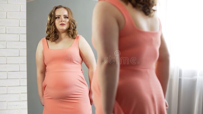 Το θηλυκό συν-μεγέθους που κοιτάζει στον καθρέφτη, που ανατρέπεται για το βάρος της, υφίσταται τις αβεβαιότητες στοκ φωτογραφία με δικαίωμα ελεύθερης χρήσης
