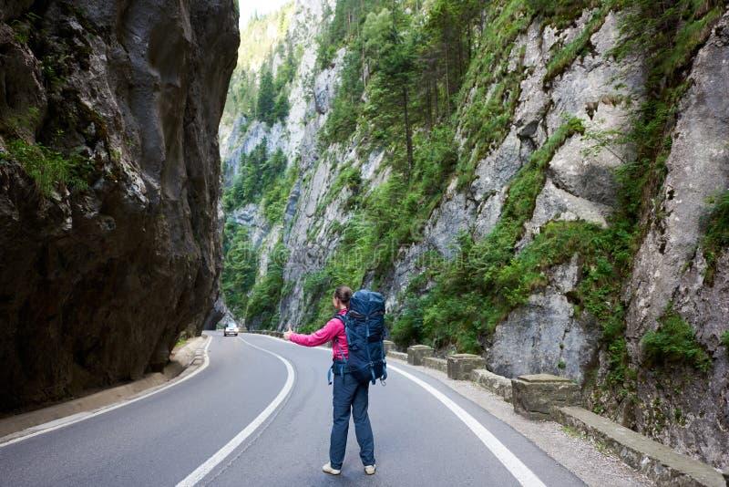 Το θηλυκό τουριστών πιάνει το αυτοκίνητο στο δρόμο στο φαράγγι Bicaz στοκ φωτογραφία