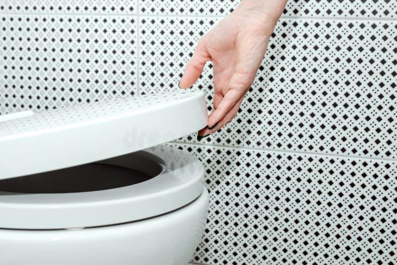 Το θηλυκό χέρι ανυψώνει το καπάκι του κύπελλου τουαλετών, κινηματογράφηση σε πρώτο πλάνο Η έννοια της προσωπικής υγιεινής στοκ φωτογραφία με δικαίωμα ελεύθερης χρήσης