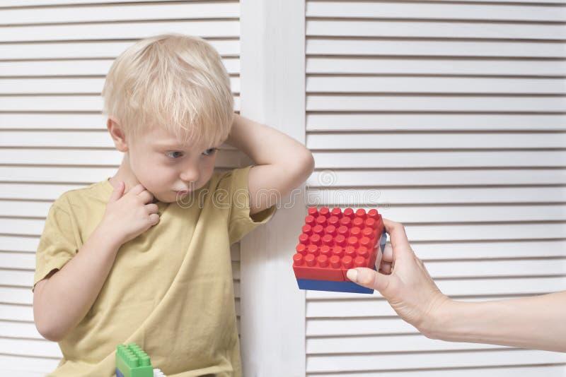 Το θηλυκό χέρι δίνει σε ένα ξανθό αγόρι έναν σχεδιαστή Παιχνίδι στοκ φωτογραφία με δικαίωμα ελεύθερης χρήσης
