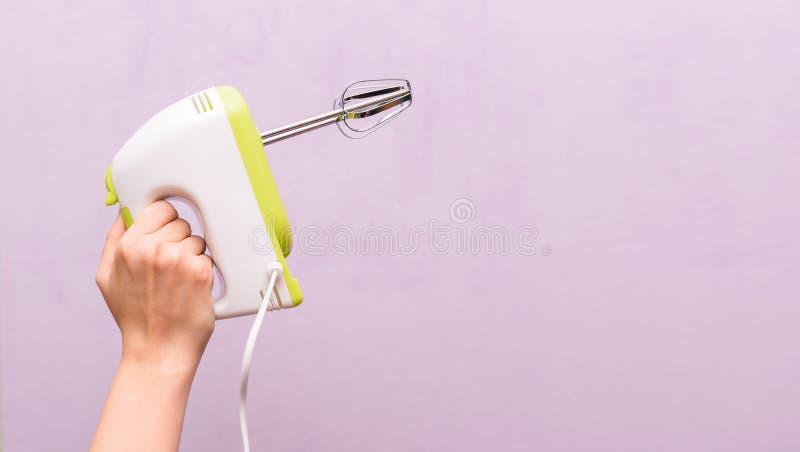 Το θηλυκό χέρι κρατά έναν αναμίκτη Ηλεκτρική συσκευή κουζινών σε ένα πορφυρό υπόβαθρο Νοικοκυρά γυναικών Κενό διάστημα για το κεί στοκ εικόνα με δικαίωμα ελεύθερης χρήσης