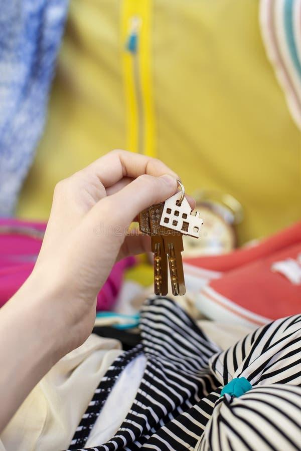 Το θηλυκό χέρι κρατά τα κλειδιά, keychain σπίτι στοκ εικόνες