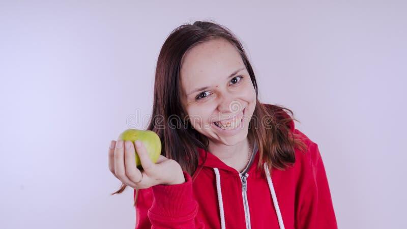 Το θηλυκό χέρι κρατά τα πράσινα φρούτα απομονωμένα στο άσπρο υπόβαθρο, κλείνει επάνω Το πρόσωπο κοριτσιών κρατά το φρέσκο μήλο Έν στοκ φωτογραφία