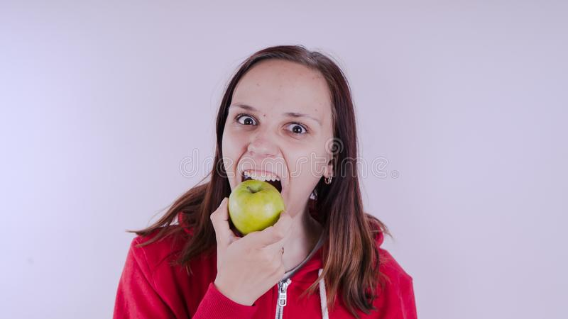 Το θηλυκό χέρι κρατά τα πράσινα φρούτα απομονωμένα στο άσπρο υπόβαθρο, κλείνει επάνω Το πρόσωπο κοριτσιών κρατά το φρέσκο μήλο Έν στοκ εικόνες