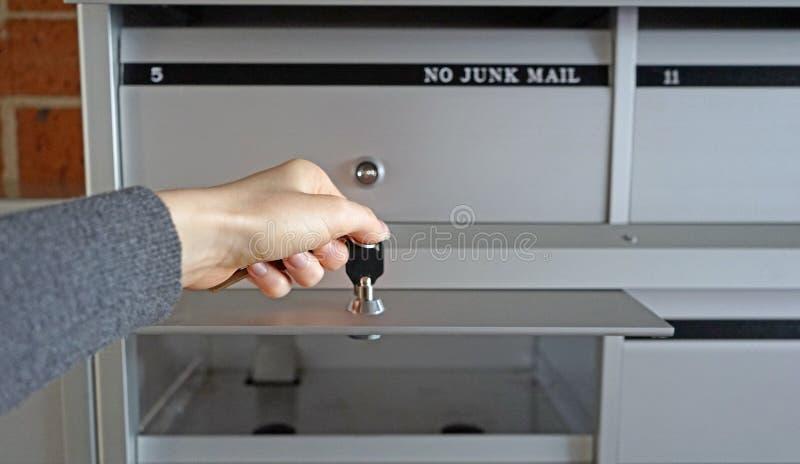 Το θηλυκό χέρι με τα κλειδιά, νέα γυναίκα άνοιξε την ταχυδρομική θυρίδα της για τα νέα ταχυδρομικά τέλη στοκ φωτογραφίες