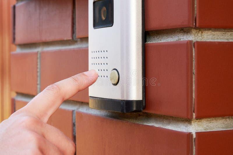 Το θηλυκό χέρι πιέζει ένα κουμπί doorbell με την ενδοσυνεννόηση στοκ εικόνες