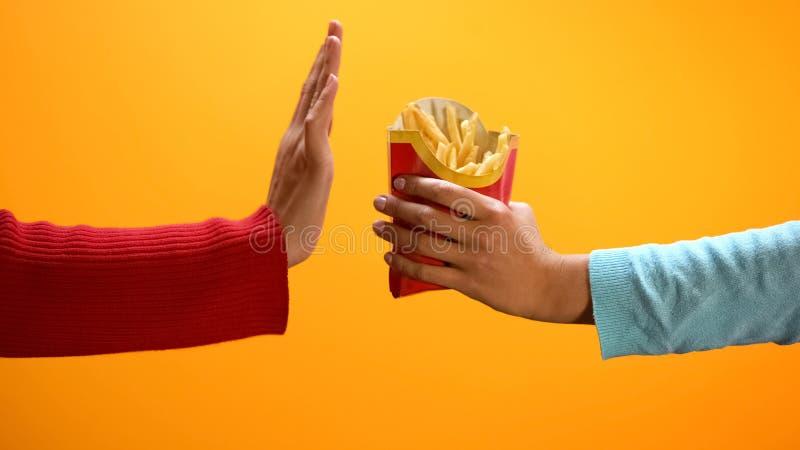 Το θηλυκό χέρι που παρουσιάζει χειρονομία στάσεων στο κίτρινο υπόβαθρο, άρνηση τρώει τις τηγανιτές πατάτες στοκ εικόνες