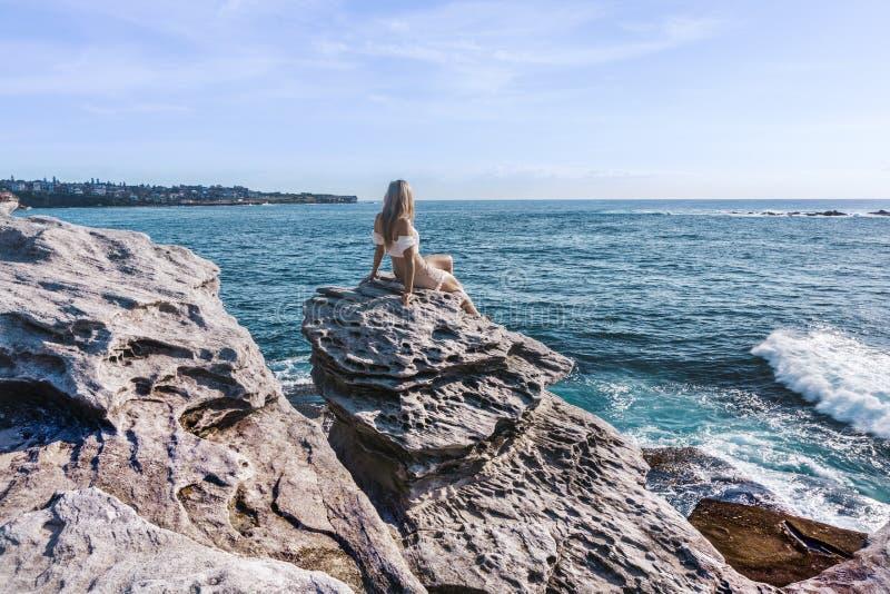 Το θηλυκό χαλαρώνει σκαρφαλωμένος σε έναν βράχο απολαμβάνοντας τα παράκτια τοπία στοκ εικόνες