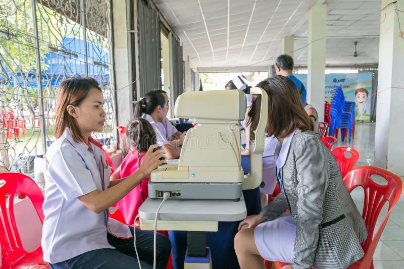 Το θηλυκό Optictian που εξετάζει ένα καλό νέο μάτι νοσοκόμων ` s στη COM στοκ φωτογραφία
