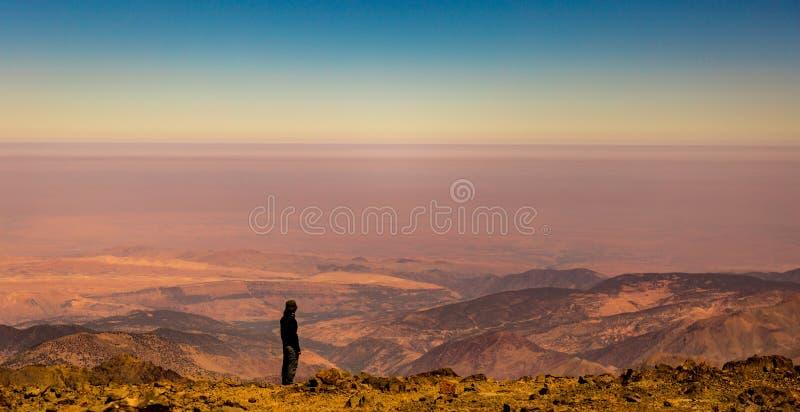Το θηλυκό trekker απολαμβάνει τη θέα από την κορυφή Jbel Toubkal, βουνά ατλάντων, Μαρόκο στοκ φωτογραφία