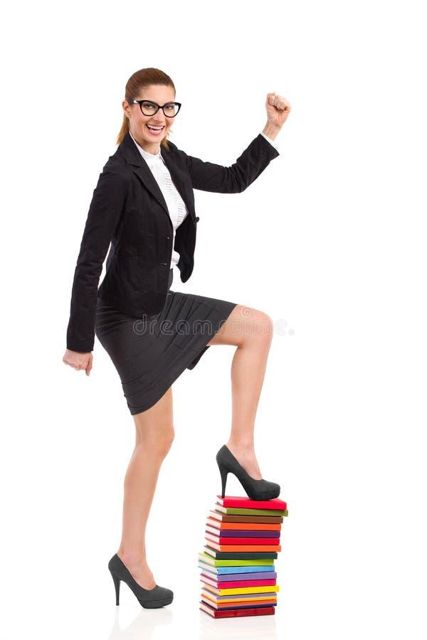 Το θηλυκό κομψότητας αναρριχείται μέχρι το σωρό των βιβλίων. στοκ φωτογραφία