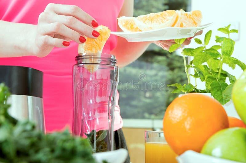 Το θηλυκό χέρι βάζει το πορτοκάλι στο μπλέντερ στοκ εικόνες με δικαίωμα ελεύθερης χρήσης