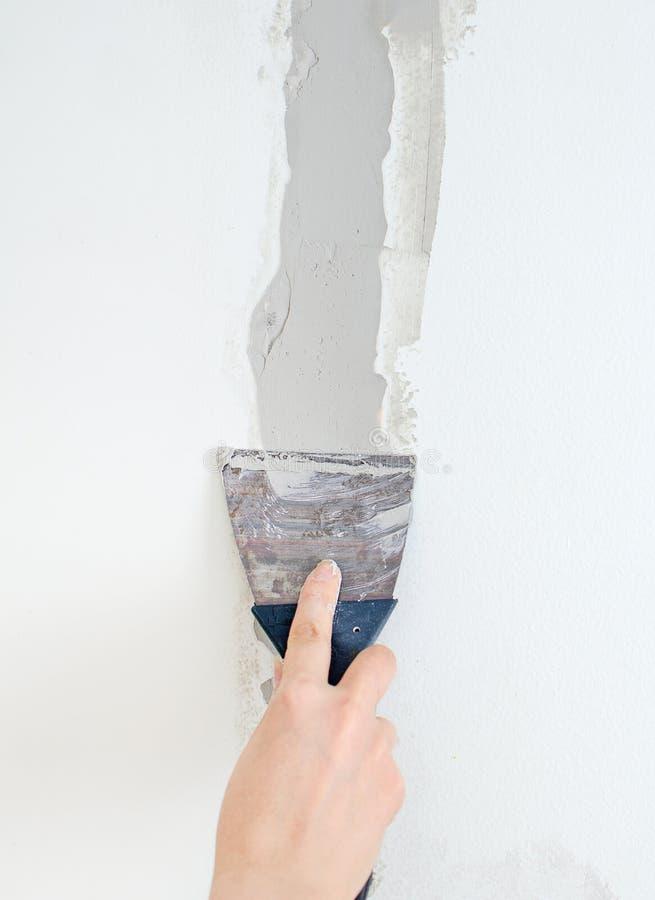 Το θηλυκό χέρι επισκευάζει τον τοίχο στοκ εικόνες με δικαίωμα ελεύθερης χρήσης