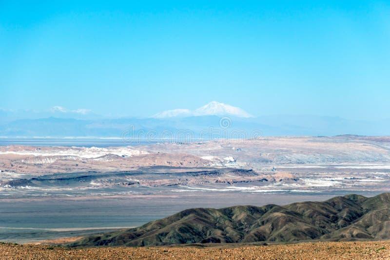 Το θολωμένο υπόβαθρο του τοπίου ερήμων Atacama με τα χιονοσκεπή των Άνδεων ηφαίστεια, αλατίζει επίπεδο και κάποια βλάστηση στον ο στοκ εικόνες